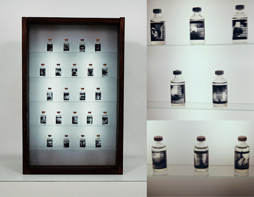An installation featuring many small bottles in a mirrored cabinet