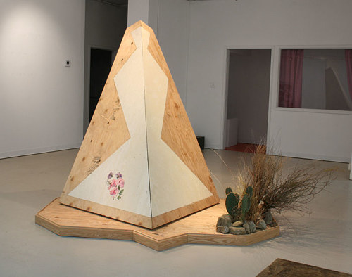 An installation made from plywood, cement and plants