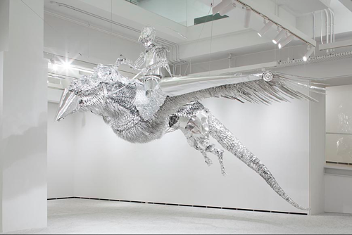 A tinfoil sculpture of a figure riding a bird