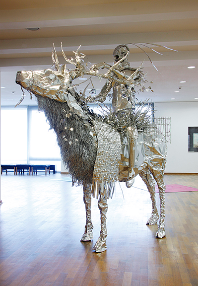 A photo of an aluminum foil sculpture of a skeletal figure on horseback