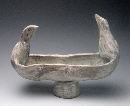 A photo of a ceramic bowl with a sculpted bird on either side