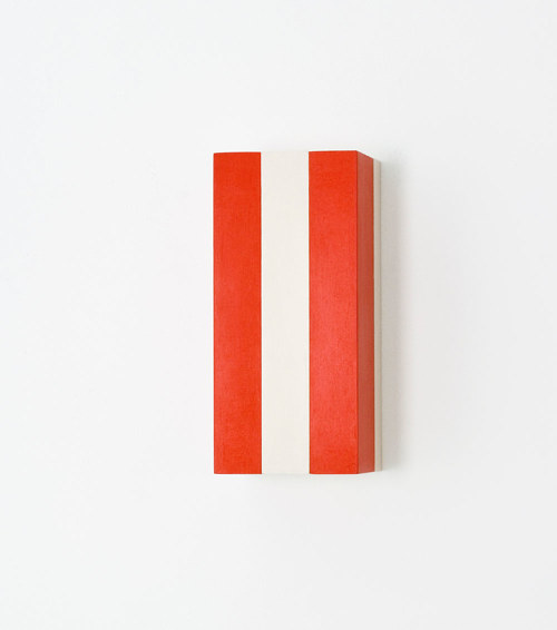 A painting of red and white stripes on a small wood block