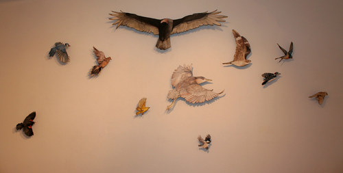 A photo of a wall installation with different birds in flight