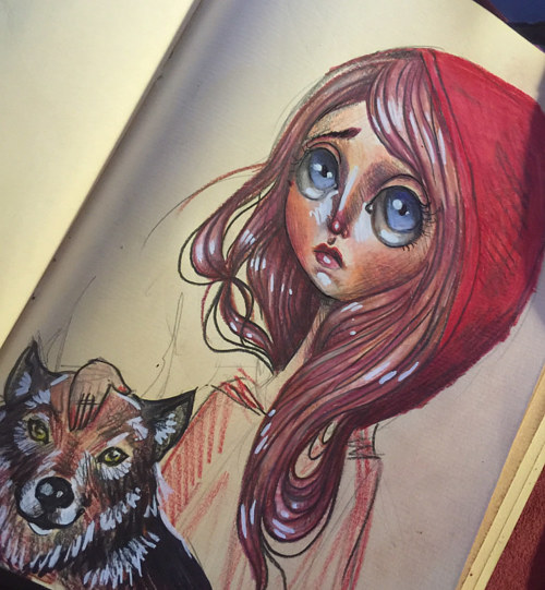 A sketchbook drawing of red riding hood with a pet wolf