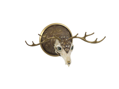A sculpture of a tiny deer's head with a skull and antlers