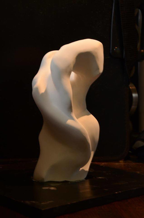 A sculpture of an abstracted human torso in white plaster