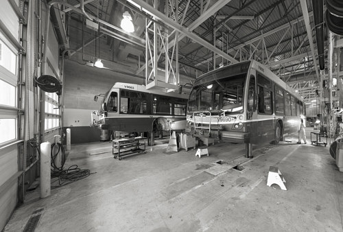 A photograph of city buses being serviced at a depot