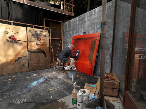 A photo of David Lynch painting in his studio