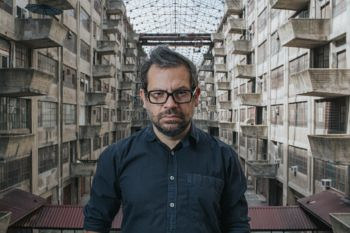 Pedro Reyes standing in the Brooklyn Army Terminal