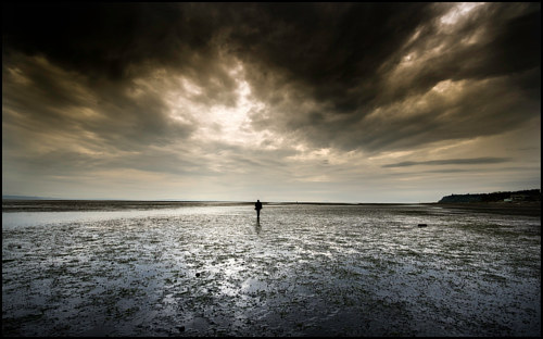 A photograph of a lone figure on a deserted beach