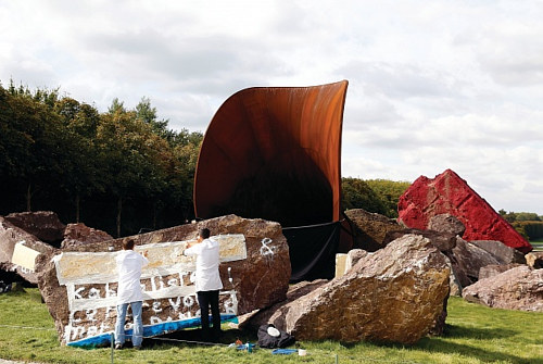A photo of workers covering graffiti on Anish Kapoor's Dirty Corner
