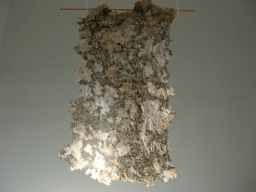 An artwork made from a drape of buried cotton fabric