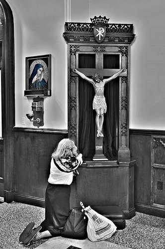 Photo of girl kneeling by crucifix