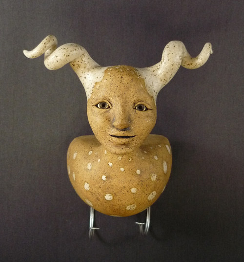 A sculpture of an antelope with a human face