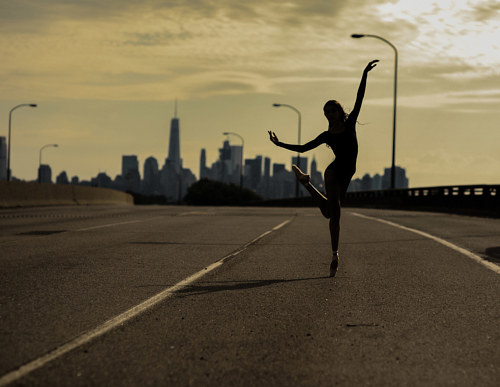 A photograph of a ballerina dancing on a bridge at sunset