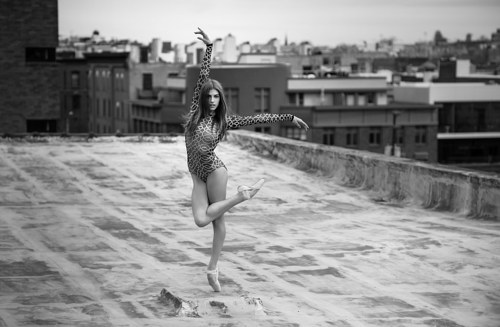 A photograph of a ballerina dancing on a rooftop