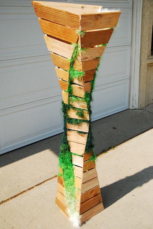 A sculpture made from wood planks and green thread