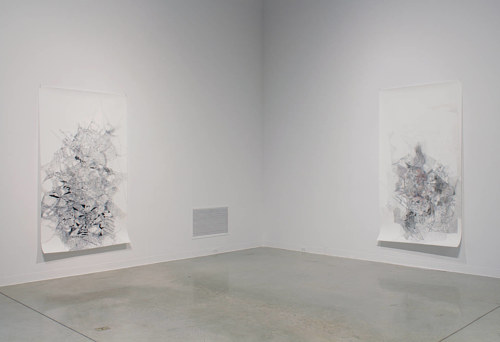 A photo of two drawings installed in an art gallery