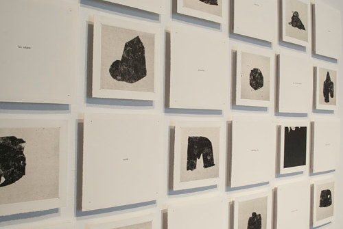 An installation view of an artwork consisting of silhouetted images on paper