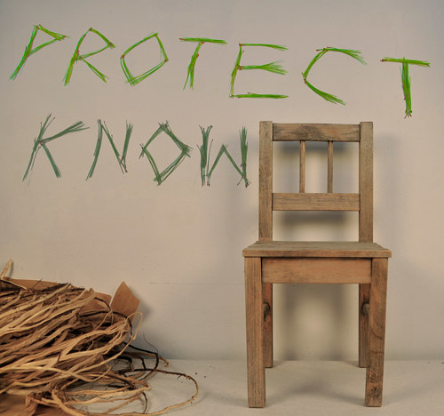 A photo of an installation featuring a chair and pine needles spelling a word