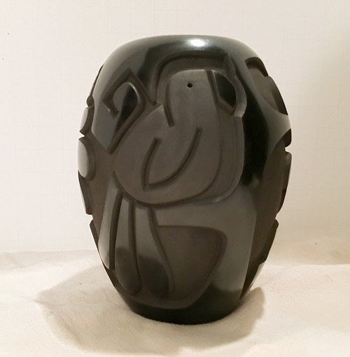 A black clay pot with a parrot carved into it