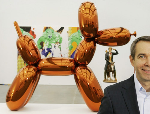 Jeff Koons poses beside an edition of Balloon Dog