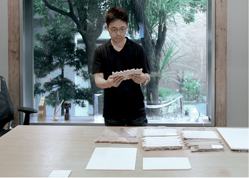 A photograph of Tokujin Yoshioka working in his studio