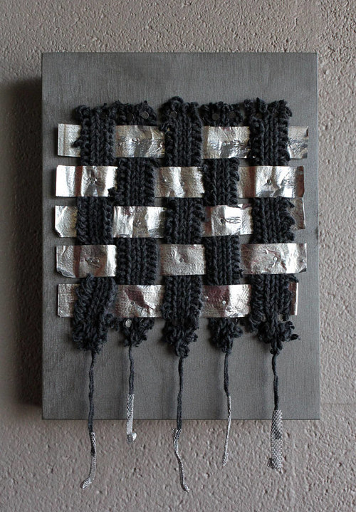 A mixed media work with a grid pattern of fabric and other material