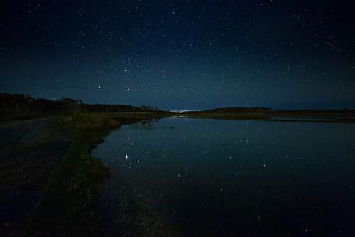 A photograph of the night sky over a still body of water