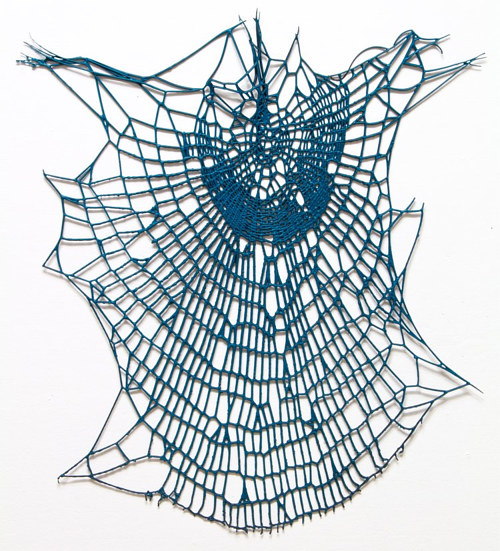 A lacquered spider web hung on a white gallery wall