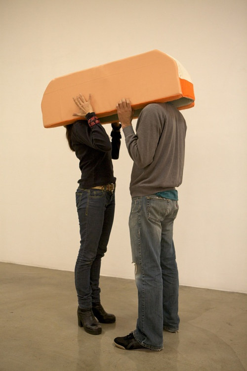 A photo of two people interacting with a Liz Nurenberg sculpture