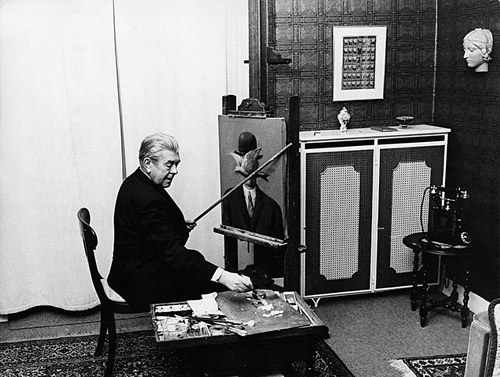 A photo of Rene Magritte at work in his studio