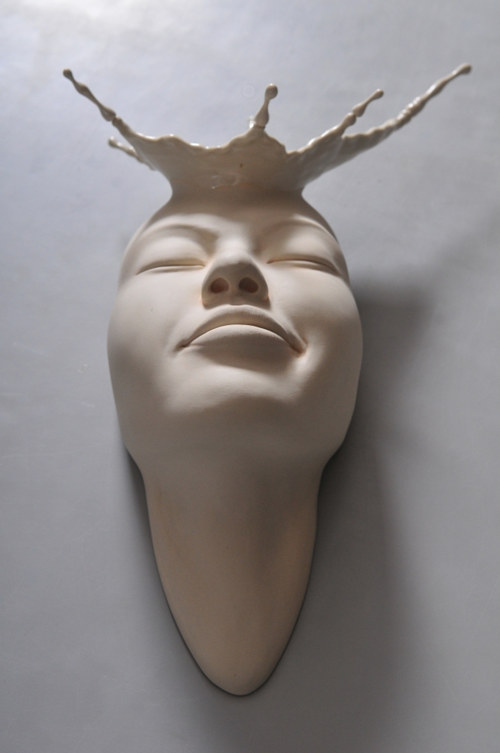 A wall-hanging sculpture of a face by Johnson Tsang