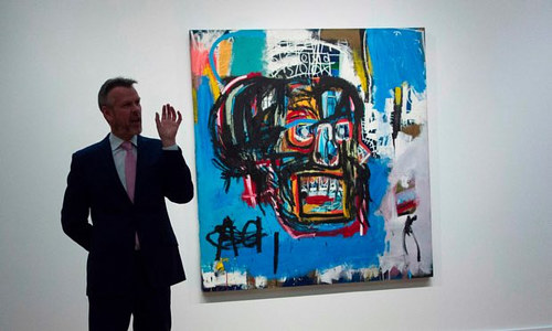 A photo of a Sotheby's auctioneer next to an untitled Basquiat