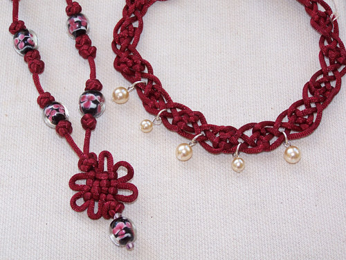 A selection of handmade jewelry with red cording