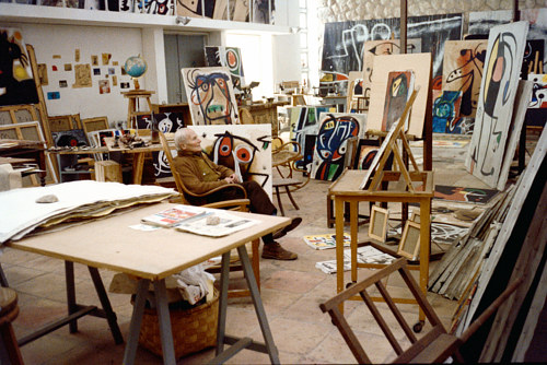 A photo of Joan Miro surrounded by paintings in his studio in Mallorca