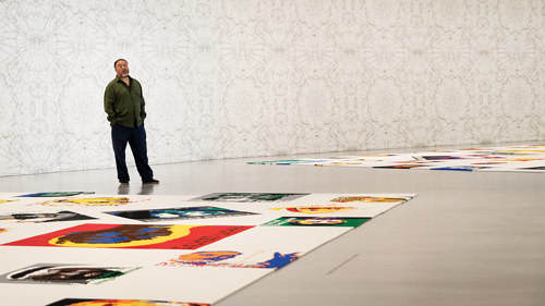 A photo of Ai Weiwei standing surrounded by his Lego portraits