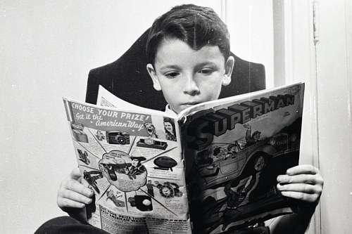 A photo of a German refugee reading a Superman comic in the 1940s