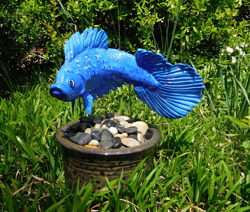 A blue fish sculpture situated in an outdoor flower pot