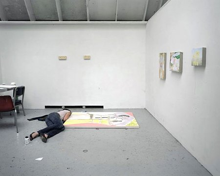 woman lying next to painting on studio floor