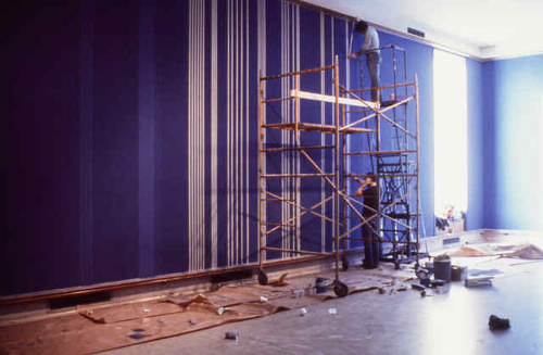 A photo of studio assistants helping to paint a 1981 Gene Davis work
