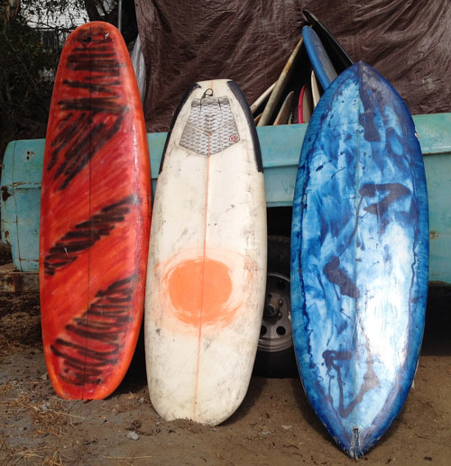 A photo of three hand-painted surfboards