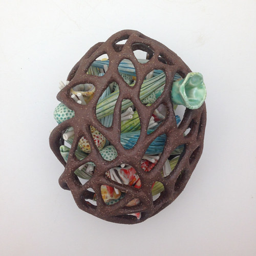 A sculpture of colorful objects trapped in a sculpted structure