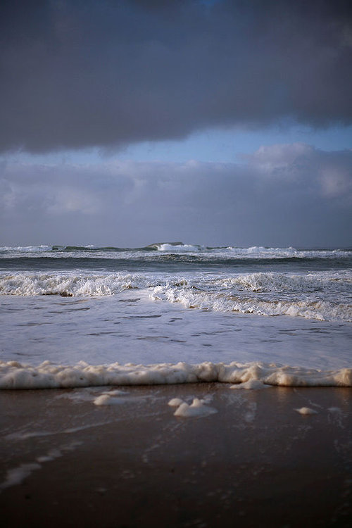 photo of sand and waves coming in
