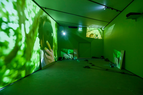 A photo of a room installation featuring a large screen projection and green light