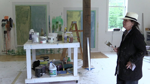 A photo of Pat Stier painting in her studio