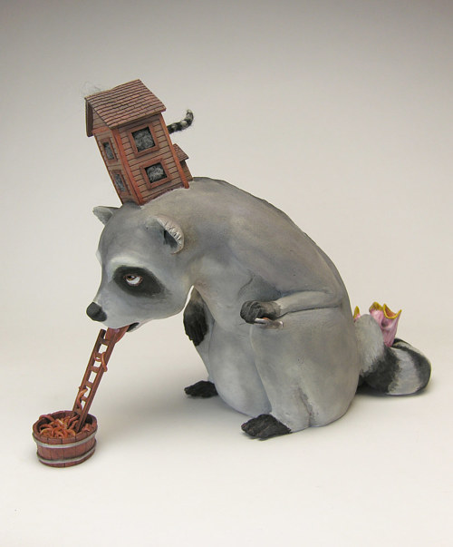 A sculpture of a raccoon with a small house on its back