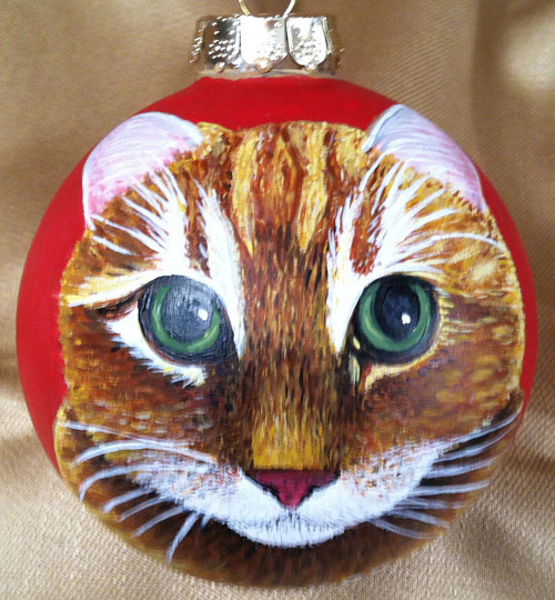 A glass ornament painted with a cat's face