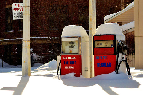 A photograph of two gas pumps under the snow