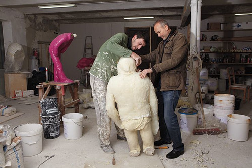 A photo of Erwin Wurm with an assistant in his studio